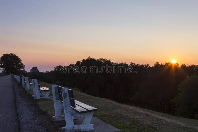 Row of deserted park benches on the Plains of Abraham at sunrise, Quebec City, Quebec, Canada. Row of deserted park benches on the Plains of Abraham at sunrise royalty free stock photos