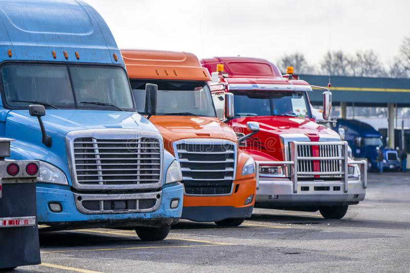 Row of different big rigs semi trucks on truck stop parking lot waiting for continuation of the road routes stock photos