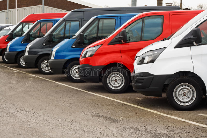 Used van sales. Row of different marques of commercial vehicles or vans for retail sale on a motor dealers lot all logos removed stock image