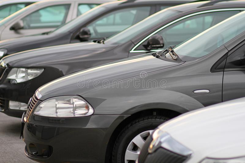 Business new cars parked ona parking in front of motor dealer store. Row of different modern new cars for retail sale on a motor dealers forecourt, all logos royalty free stock photo