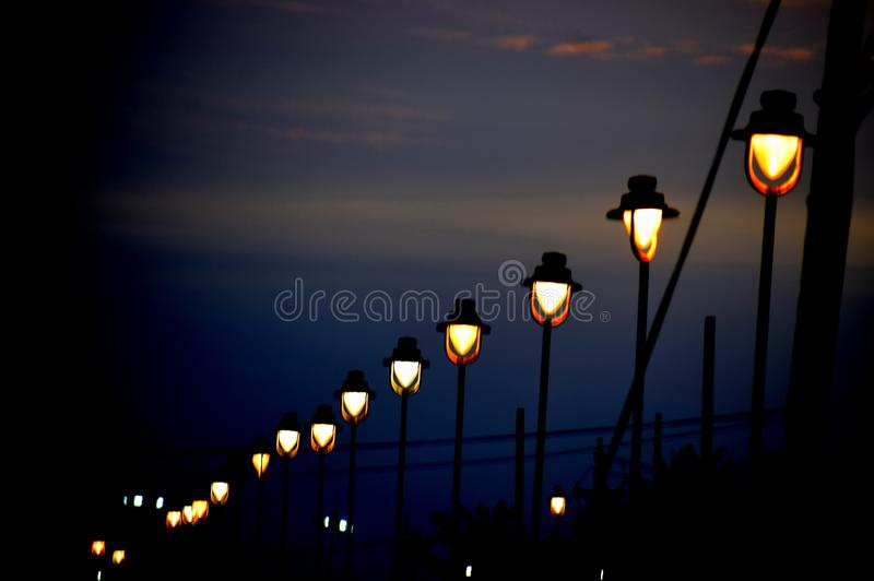 Row of dim lights near a beach in night royalty free stock images