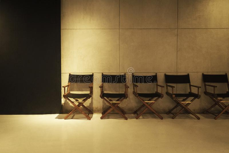 Row of director`s chair on gray cement background in studio. stock images
