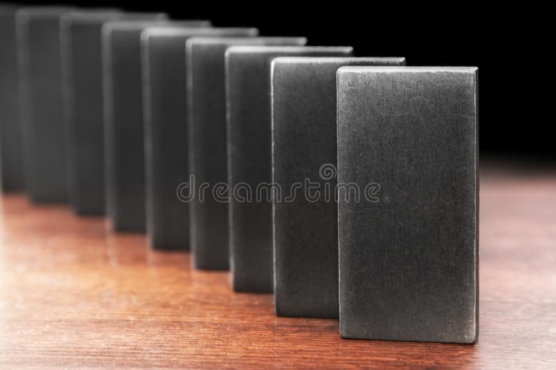 Domino effect. Row of domino tiles symbolizing fragile system stock photography