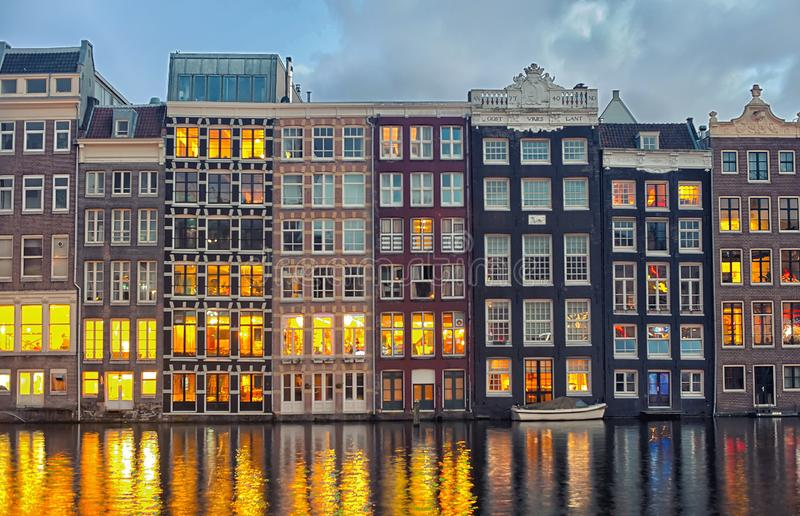 Row of Dutch houses at Central canal Damrak Amsterdam, Netherlands at twilight stock image