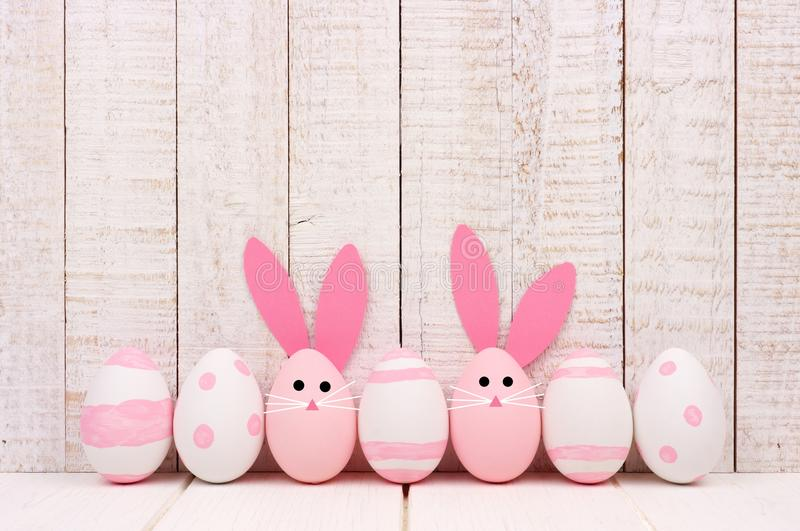 Easter eggs against white wood, two with bunny faces and ears royalty free stock photo
