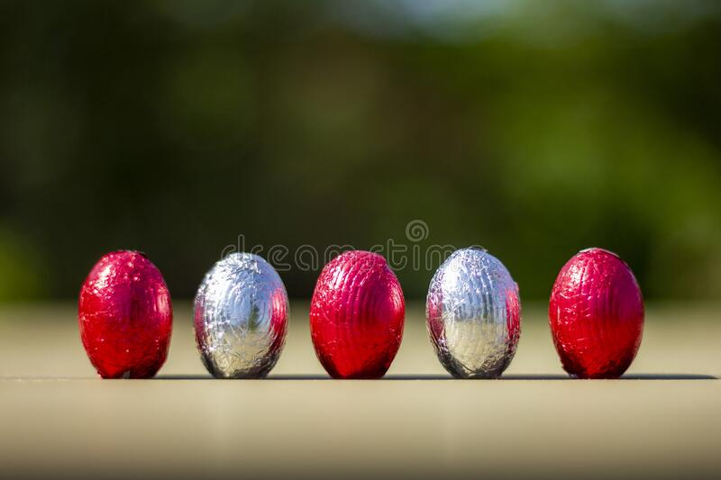 A row of easter eggs standing upright on a table. The eggs are made of chocolate and are wrapped in colorful tin foil stock photo