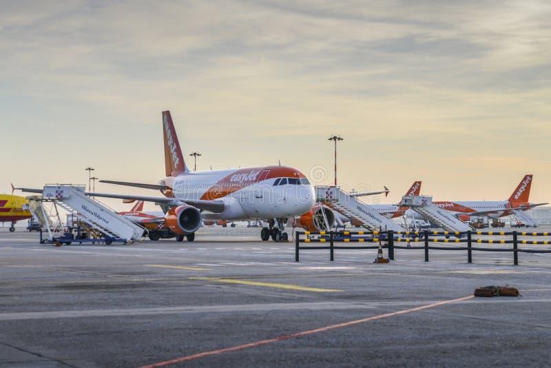 Row of Easyjet Airbus A320 airplanes on the tarmac at Milan Malpensa airport, servicing short-haul flights in Europe. Milan Malpensa, Italy - November 21st, 2017 stock photos