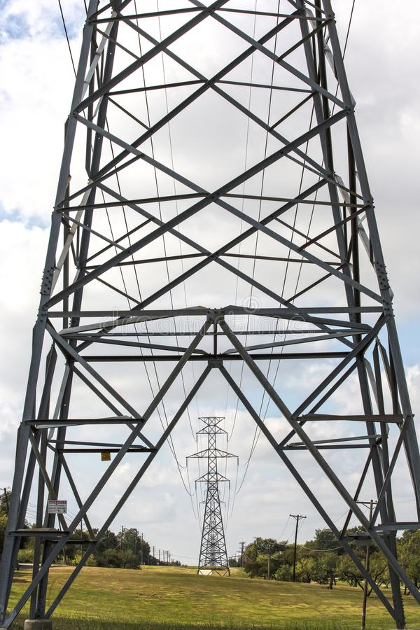 Row of electrical transmission towers in Texas. High voltage electrical transmission tower in the foreground and other towers seen through it, in the background stock photos
