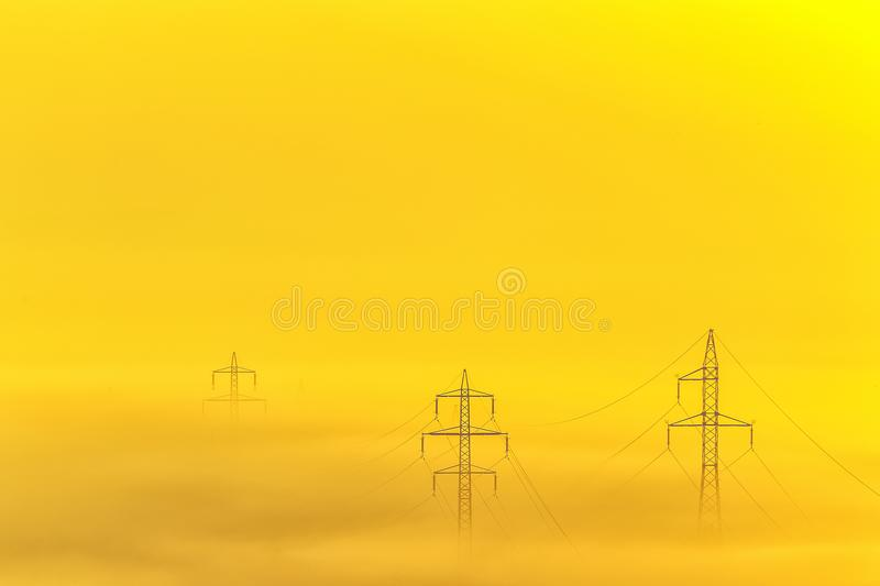 Row of electricity poles lines on field in morning fog during sunrise in the morning. Row of electricity poles lines on field in morning fog during sunrise in stock photography