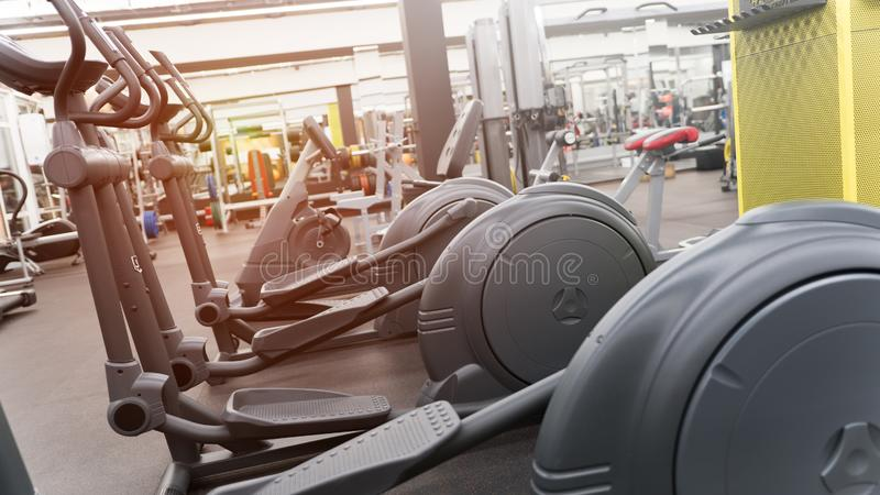 Row of elliptical trainers in big new gym at angle royalty free stock photography