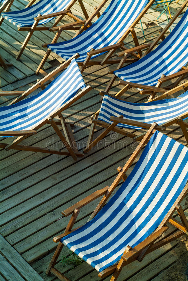 Row Of Empty Blue And White Striped Beach Chairs Stock Photo