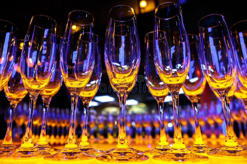 A row of empty champagne glasses. Illuminated with yellow light stock photos