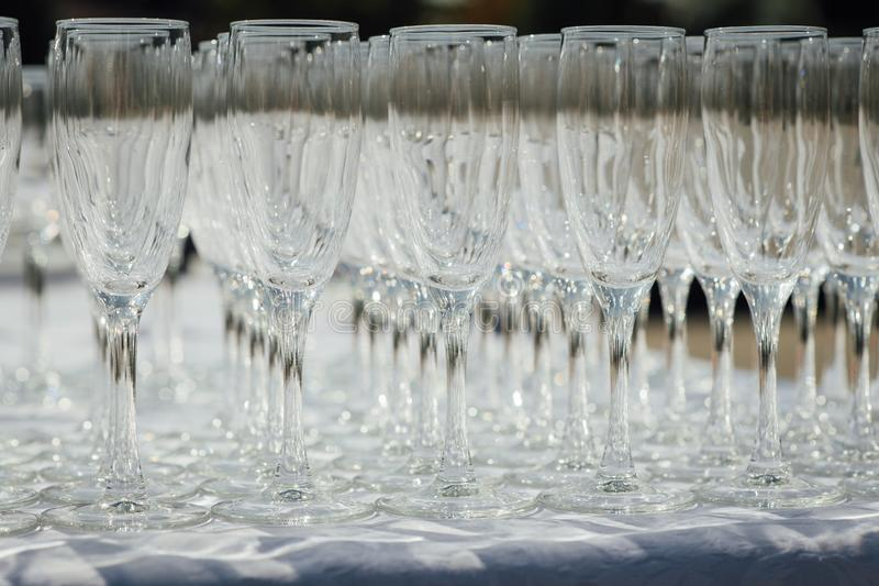 A row of empty champagne glasses on table. Banquet setting stock image