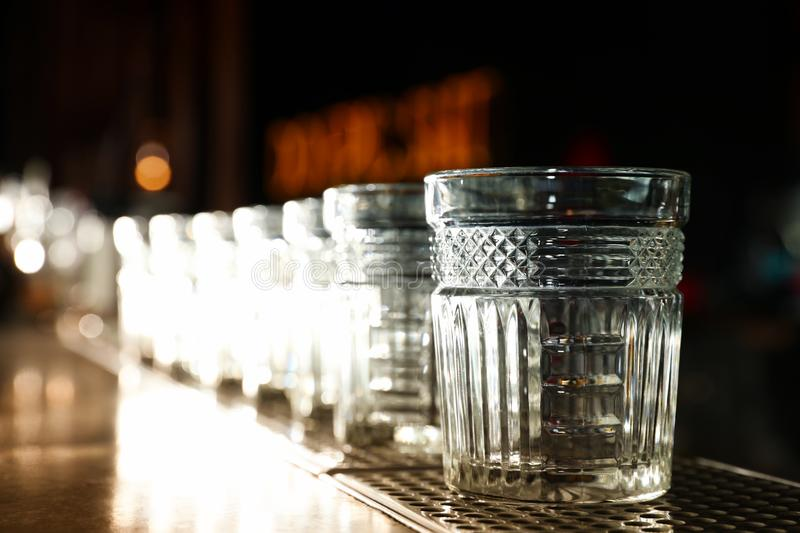 Row of empty clean glasses on counter in bar. Space for text stock photo
