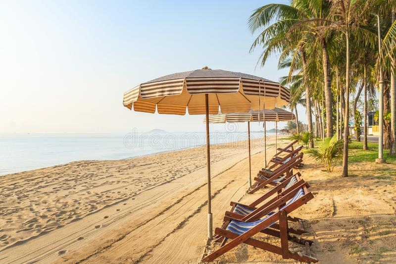 Row of empty wooden beach chairs with parasols on tropical sandy beach in the morning. Relax leisure summer holidays concept stock photos