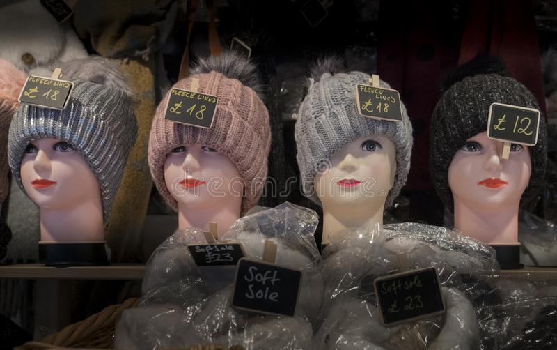 Knitted winter hats. A row of female mannequin heads on a market stall wearing a knitted hat stock photo