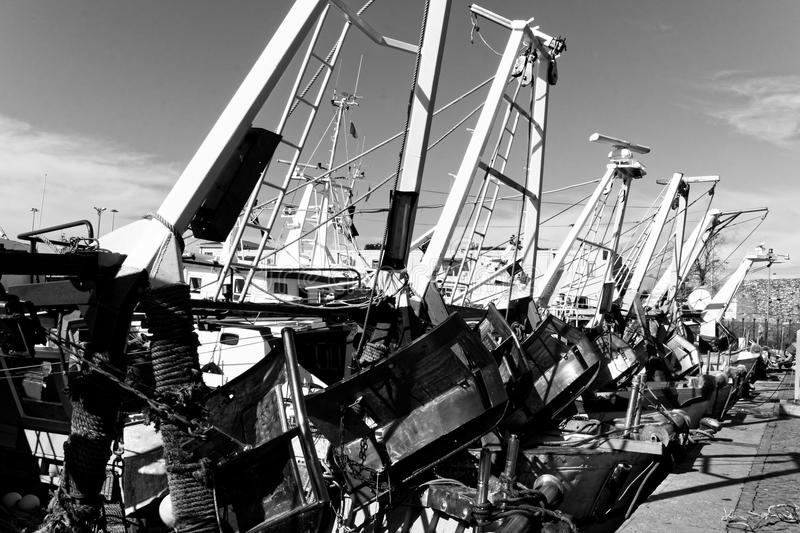 Row of fishing vessels with jumbled fishing tackle stock photo