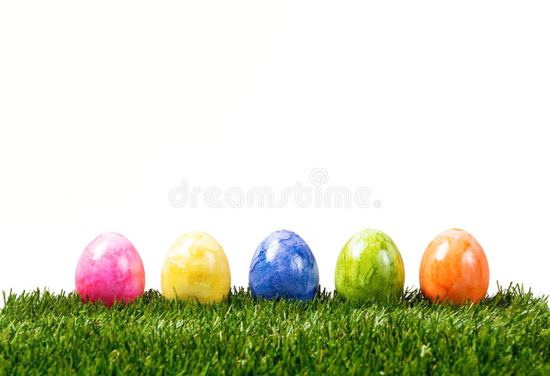 A row of five colorful easter eggs on green grass isolated on white royalty free stock photography