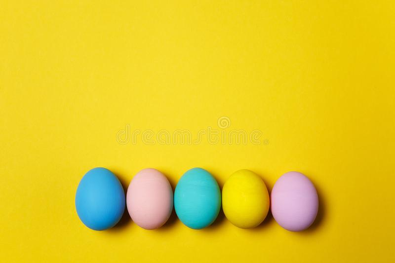 Row of five colorful pastel monophonic painted Easter eggs isolated on yellow background for card or postcard. Happy royalty free stock photo
