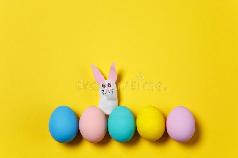Row five colorful pastel monophonic painted Easter eggs isolated on yellow background, white bunny or rabbit. Happy stock image