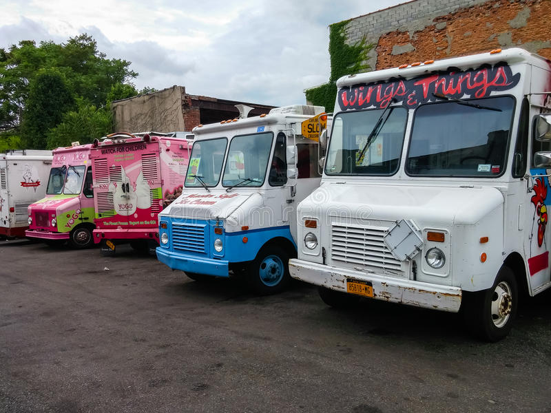 A row of food and ice cream trucks on a parking lot in New York stock image
