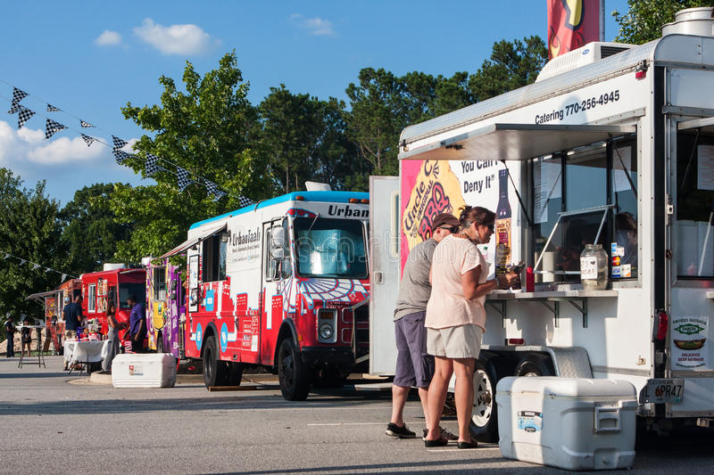 Row Of Food Trucks Serves Customers At Georgia Festival. Kennesaw, GA, USA - August 27, 2016: A row of colorful food trucks serves customers at the Great stock photography