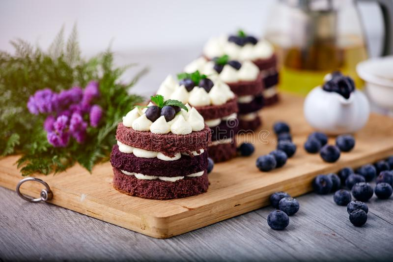 Row of four brown cakes with blue berry on top placing together pink flower and berry as decorated item stock photo
