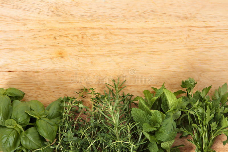 Row of fresh herbs on an old wooden chopping board. Space for copy stock photography
