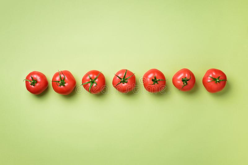 Row of fresh red tomatoes on green background. Top view. Copy space. Minimal design. Vegetarian, vegan, organic food and stock photos