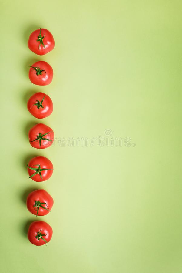 Row of fresh red tomatoes on green background. Top view. Copy space. Minimal design. Vegetarian, vegan, organic food and royalty free stock images