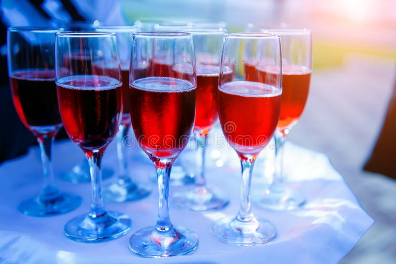 A row of glasses filled with cold champagne lined up, ready to be served. Glasses with Martini on the table - party background. Welcome drink on the wedding royalty free stock photography