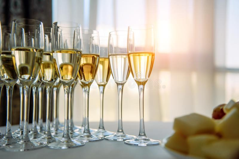 A row of glasses filled with cold champagne lined up, ready to be served. Glasses with Martini on the table - party background. Welcome drink on the wedding royalty free stock photos