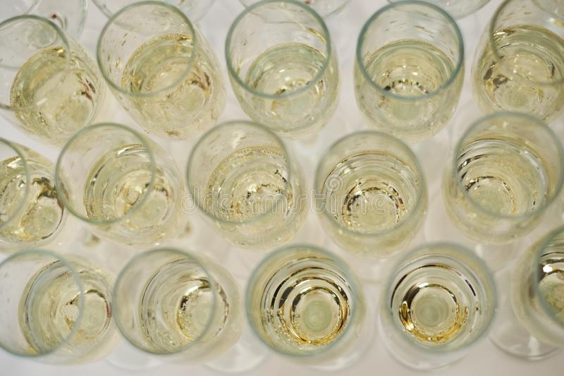Row of glasses filled with cold champagne white wine royalty free stock image