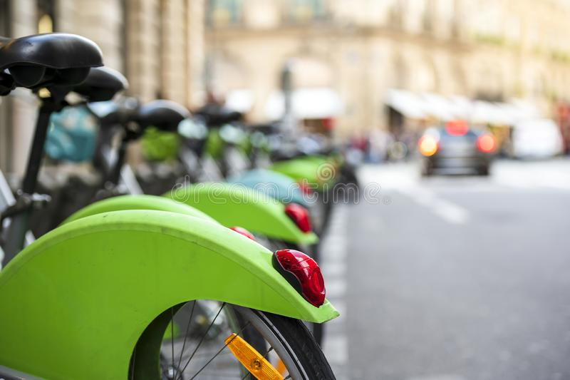 Row of green bikes for public rent stand at parking station on street in Paris ready for use. Street transportation green hybrid public rent bicycles for royalty free stock image