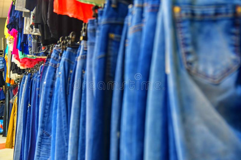 Row of hanged blue jeans in a shop. Clothes store. Shopping in fashion mall. Garments on hangers. Clothes on the store shelves. Blurred view, defocuded stock photography