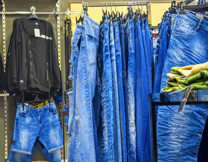 Row of hanged blue jeans in a shop. Clothes store. Shopping in fashion mall. Garments on hangers.  stock photo