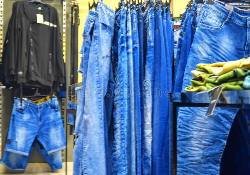 Row of hanged blue jeans in a shop. Clothes store. Shopping in fashion mall. Garments on hangers.  royalty free stock photo