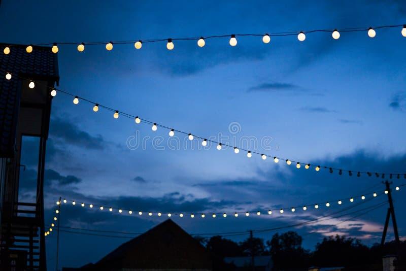 Row of hanging summer terrace lights during evening, small outdoor light bulbs. Row of hanging summer terrace lights during evening, small outdoor light bulbs stock photo
