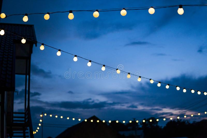 Row of hanging summer terrace lights during evening, small outdoor light bulbs. Row of hanging summer terrace lights during evening, small outdoor light bulbs stock image