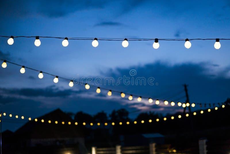 Row of hanging summer terrace lights during evening, small outdoor light bulbs. Row of hanging summer terrace lights during evening, small outdoor light bulbs stock photos