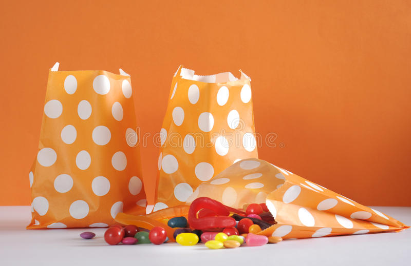 Row of Happy Halloween orange polka dot trick or treat paper bags. With multi-color candy against and orange and white background stock photography