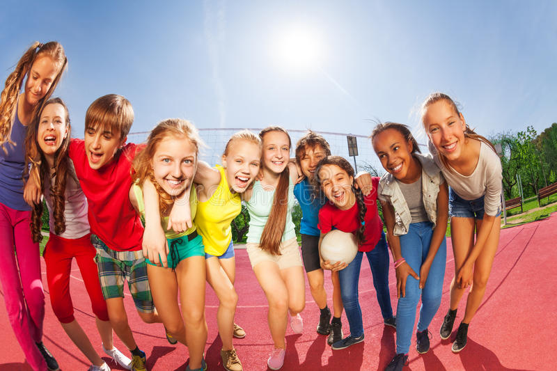Row of happy teens standing on volleyball court. Row of happy teens standing on the volleyball game court holding ball during summer sunny day royalty free stock photos