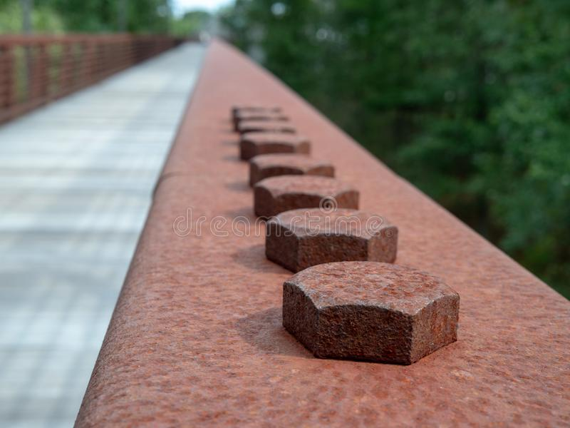 Row of hex screws in a rusted steel handrail on a wooden bridge on hiking path. Row of hex screws in a rusted steel handrail on a wooden bridge along hiking path royalty free stock photography