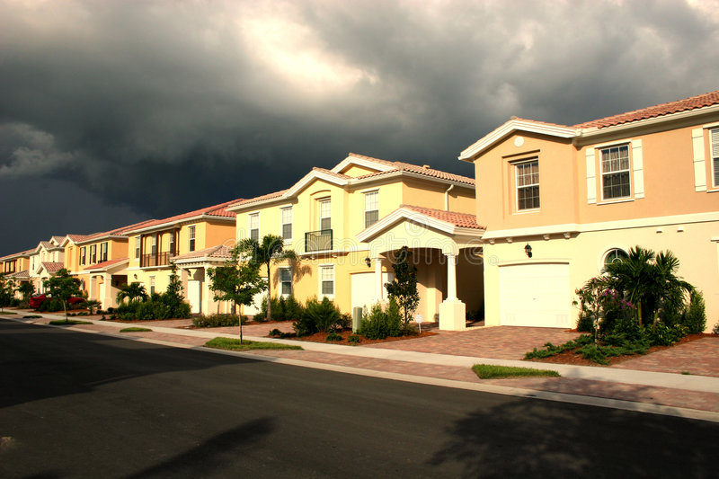 Row of Houses. Row of new peach and yellow houses with dramatic sky stock image