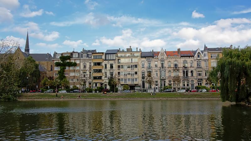 Row of houses in eclectic art nouveau style on the embankment of Ixelles lakes and Sainte-Croix church royalty free stock photo