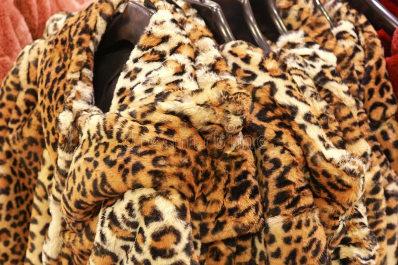 Row of jackets with leopard pattern in a store. Animal print, faux fur stock photography