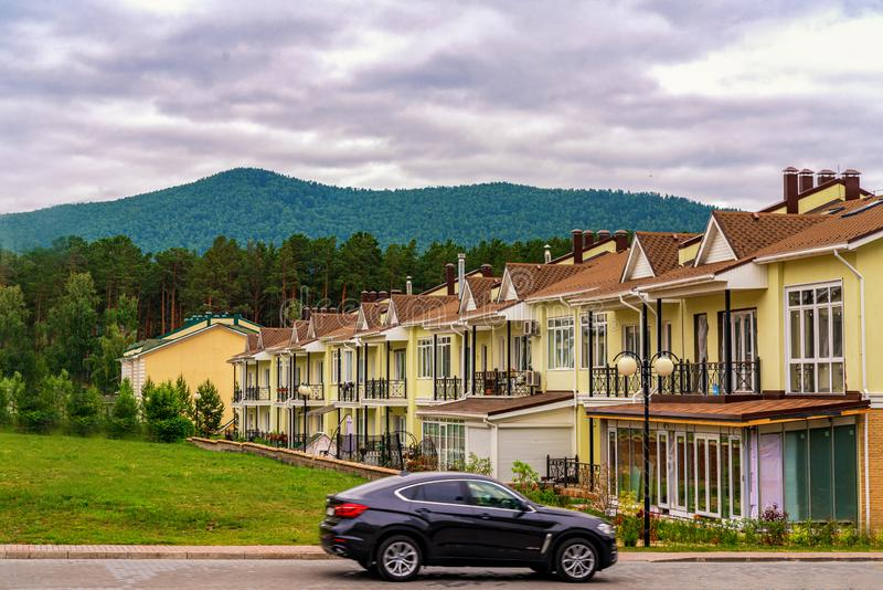 Krasnoyarsk, Russia, 14 jule 2019: A row of just finished new yellow townhouses. Residential village at the foot of the stock photography