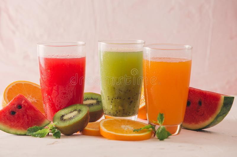 Row of kiwi, orange and water melon smoothie and various pieces stock photography