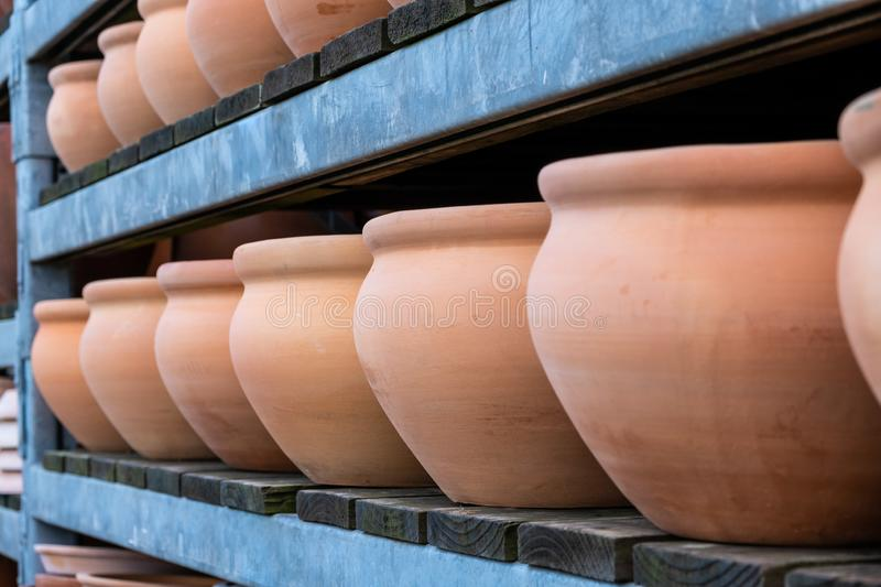 Row of large brown clay flower pots. stock photo
