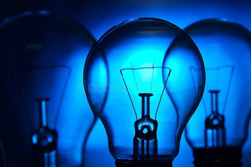 Row of light bulbs n a bright blue background stock photos